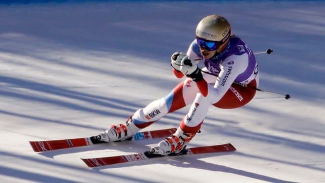 Ski-Fahrerin in der Hocke während einer Abfahrt.