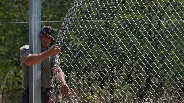 Ein Soldat befestigt einen Maschendrahtzaun.