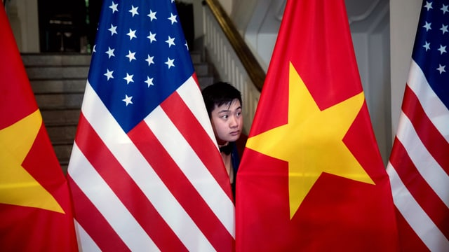 Ein Vietnamese steht zwischen der amerikanischen und der vietnamesischen Flagge.