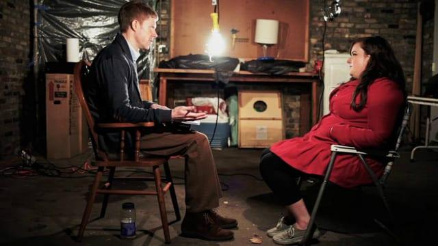 Ein Mann und eine Frau sitzen sich gegenüber und schauen sich in die Augen. Der Mann hält Stift und Papier in der Hand. Im Hintergrund sieht man Gerümpel im Schein einer Glühbirne.