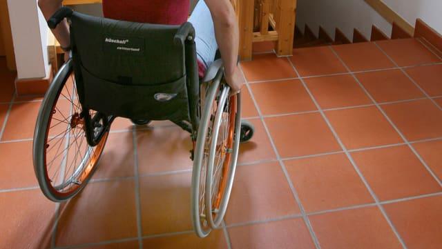 Eine Person sitzt im Rollstuhl