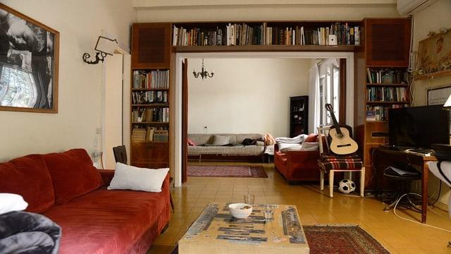 Blick in ein gemütliches Wohnzimmer. Ein rotes Sofa, viele Bücher, ein Stuhl mit einer Gitarre drauf.