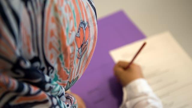 Ein Mädchen mit Kopftuch schreibt etwas auf ein Blatt Papier
