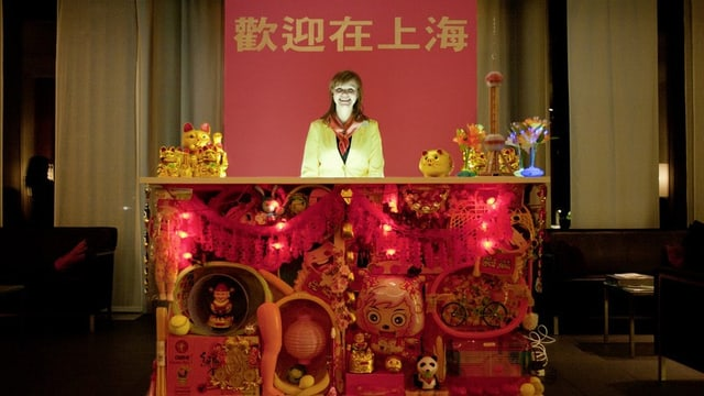Eine Frau an reich chinesisch dekorierten Rednerpult.