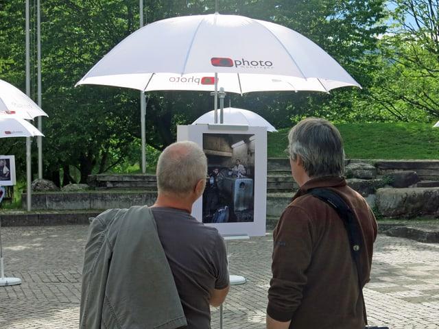 Besucher betrachten Fotos.