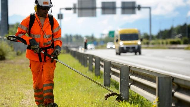 Arbeiter mäht Rasen am Rand der Autobahn
