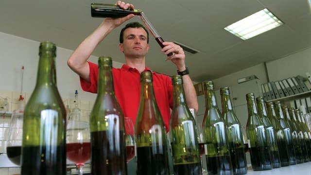 Ein Mann füllt Wein in Flaschen ab.