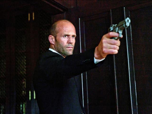 Jason Statham als Gangster Parker hält eine Pistole.