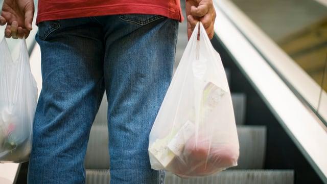 Eine Person trägt zwei Plastiksäcke