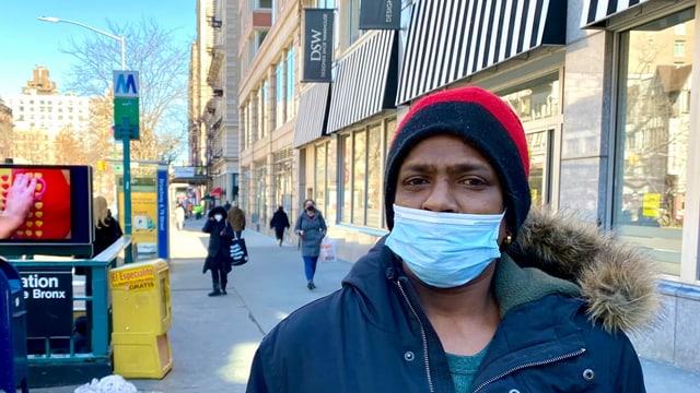 Ein Mann mit Mütze und Gesichtsmaske schaut in die Kamera.