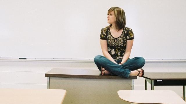Eine Lehrerin hockt auf einem Pult.