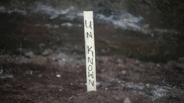 Ein Holzstäbchen mit der Aufschrift «Unbekannt» auf einem Grab