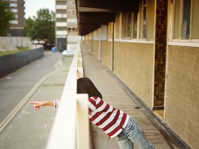Ein Mädchen vor einem etwas trostlosen Wohnblock, an ein Geländer gelehnt, auf etwas zeigend.