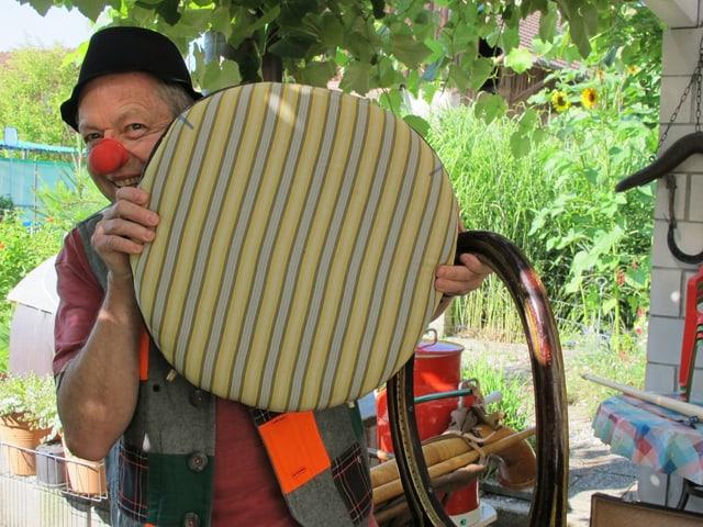 Clown hinter Stuhlkissen