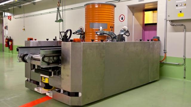 Ein Transportsystem fährt ein oranges Fass mit radioaktiven Abfällen zum Tor des Plasmaofens.
