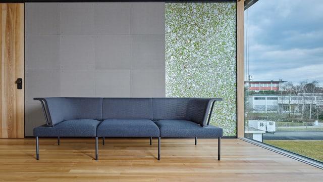 ein Sofa, das in einem offenen Wohnzimmer mit grosser Fensterwand und recyclebaren Wänden steht