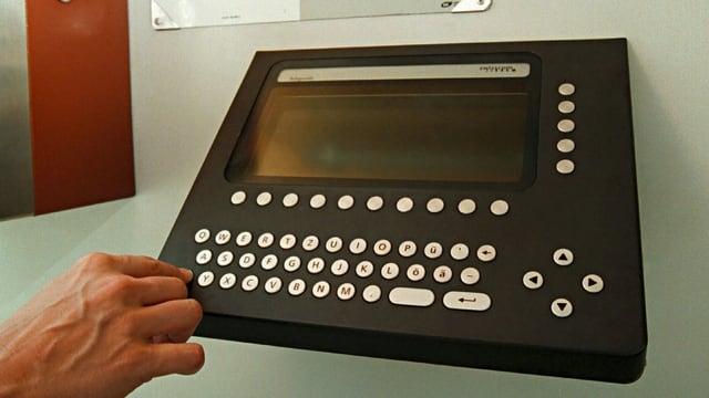 Eine Hand bedient ein elektronisches Telefonbuch.