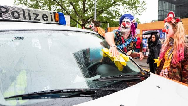Clowns putzen die Frontscheibe eines Polizeiautos
