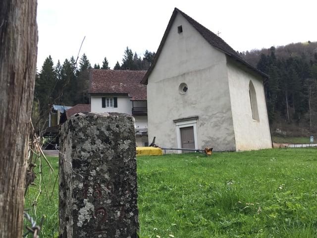 Grenzstein, dahinter Kapelle