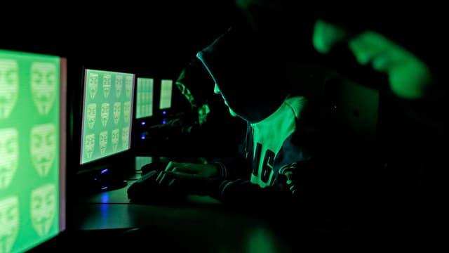 Hacker vor grünen Bildschirmen.