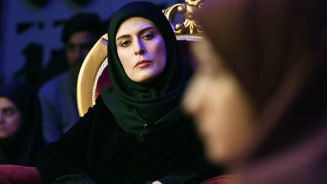 Filmszene: Eine Frau mit Kopftuch sitzt in einem pompösen Sessel und schaut ernst auf eine jüngere Frau im Vordergrund, die man nicht richtig erkennt.