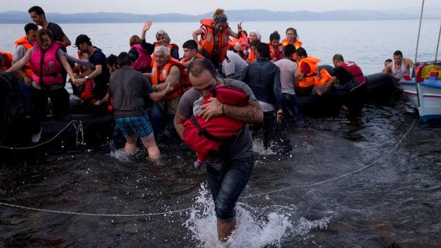 Ankunft auf der Insel Lesbos. Ein Vater hält sein Kind fest an sich gedrückt.