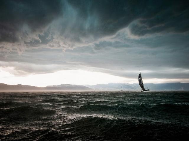 Ein Segelschiff auf einem See vor suklen Regenwolken