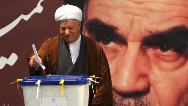 Rafsandschani, ein Mann mit weissem Turban, wirft den Stimmzettel in die Plastikurne, hinter ihm ein grosses Wandbild von Ajatollah Chomeini.