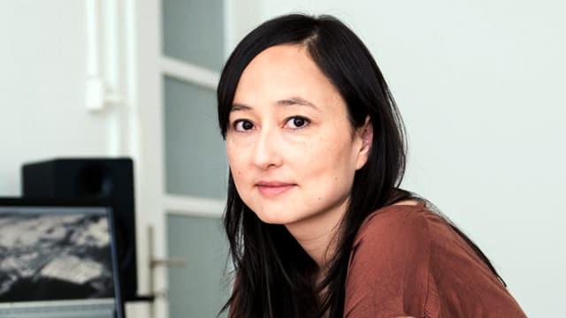 Eine junge Frau mit japanischem Gesicht und langem Haar sitzt in einem Büro.