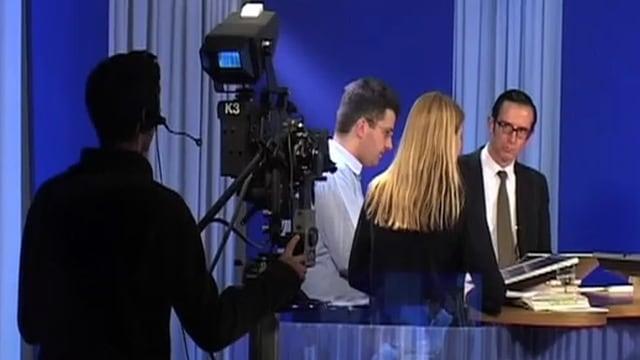 Ein Kameramann filmt drei Menschen um einen Tisch