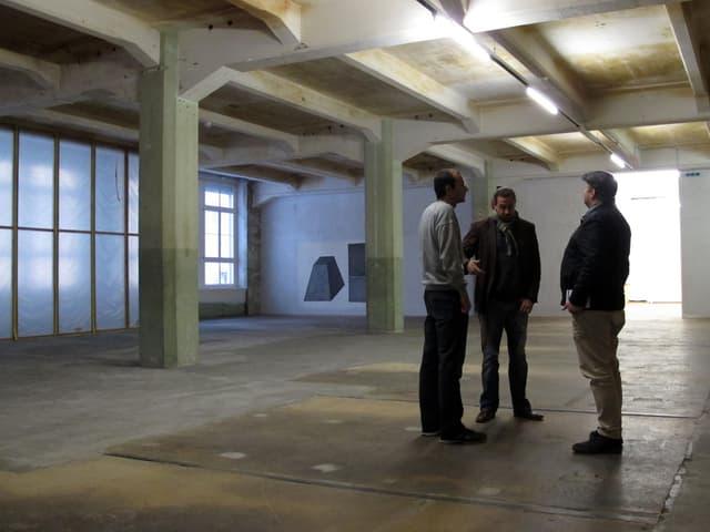 Drei Personen stehen in einem leeren Raum des Kulturzentrums Kammgarn.