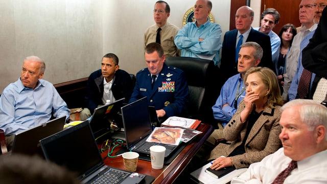 Hillary Clinton, Barack Obama, Joe Biden und andere hohe US-Verantwortliche in einem Raum.