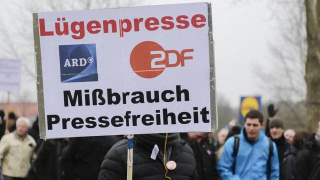 Demonstrant hält ein Schild hoch, auf dem steht: Lügenpresse ARD / ZDF, Missbrauch der Pressefreiheit.