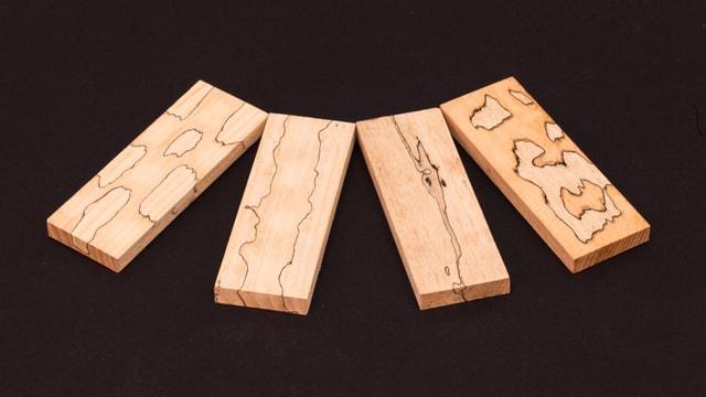 Vier Holzstücke mit unterschiedlichen Strukturen.