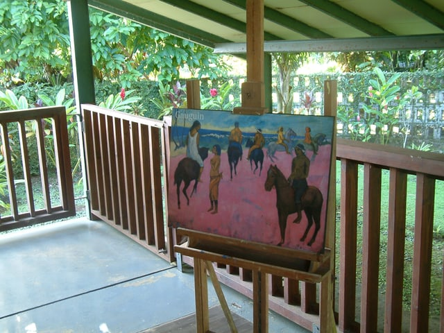 Ein Gemälde auf einer Staffelei auf einer Veranda mit Blick auf einen Garten.
