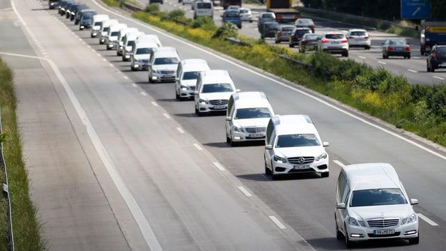 Weisse Autos, welche die Leichen der Germanwings-Opfer transportieren, fahren auf einer Autobahn