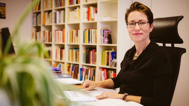 Eine Frau sitzt lächelnd an einem Schreibtisch.