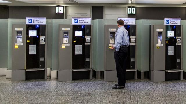 Mann bezahlt an einem Automaten am Flughafen Zürich-Kloten sein Parkhausticket