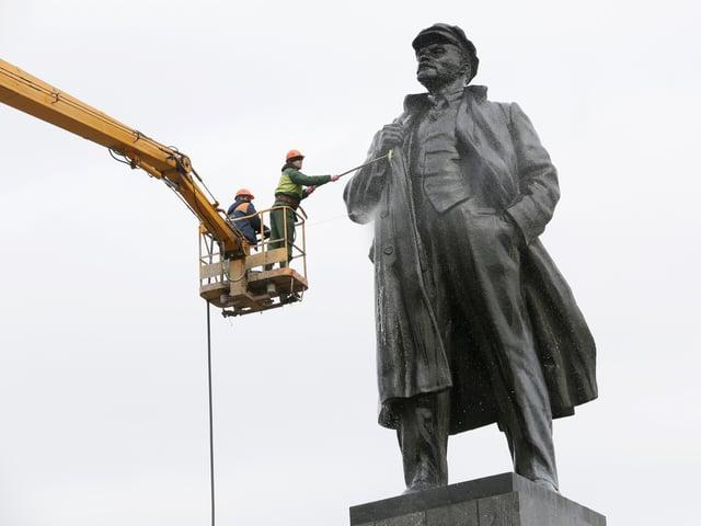 Arbeiter putzen eine gigantische Lenin-Statue