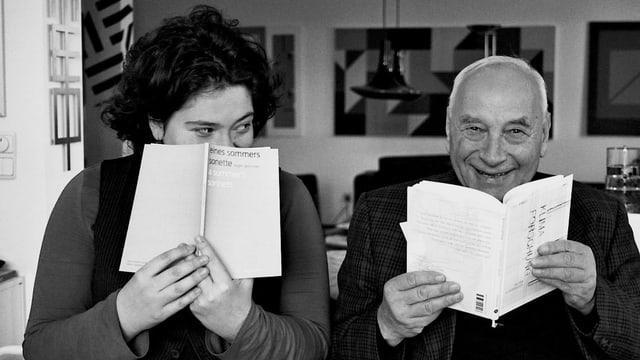 Tochter und Vater – Nora und Eugen Gomringer im Jahr 2013 verstecken sich lachend hinter Büchern