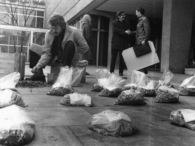 Ein Mann füllt Schrauben in Plastiksäcke am Boden ab.