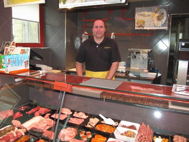 Ein Mann steht hinter eine Fleisch-Theke.