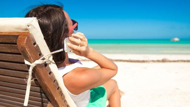 Eine Frau sitzt am Strand im Liegestuhl und telefoniert mit dem Handy