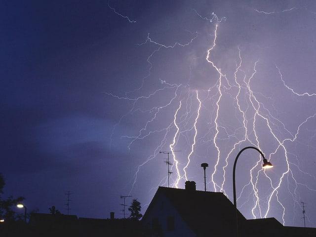 Blitze zucken aus den Wolken in Richtung Stadt.