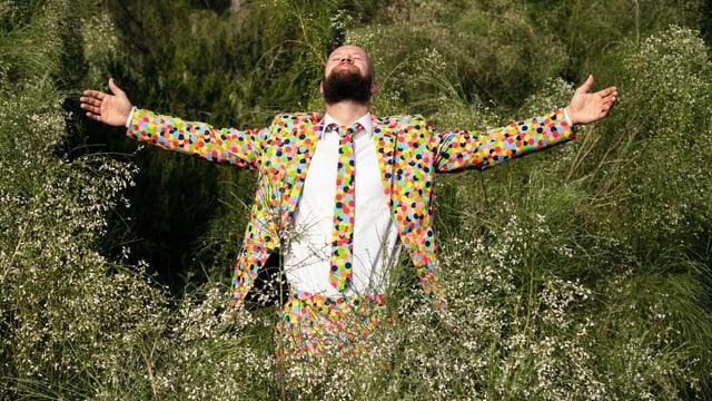 Ein Mann steht in einem bunt-gepunkteten Anzug in der Natur.