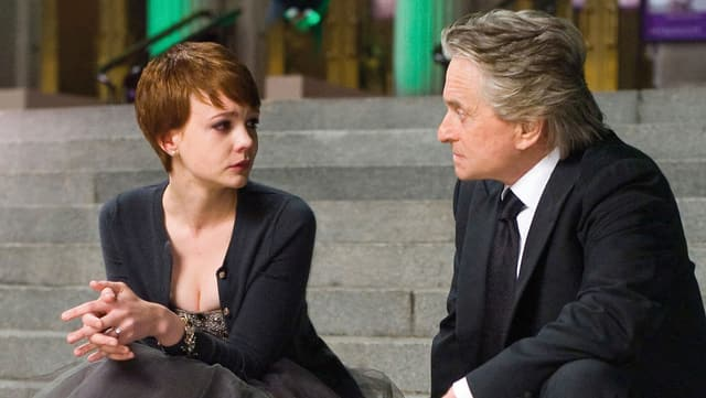 Ein älterer Mann und eine junge Frau sitzen sich auf einer Treppe gegenüber.