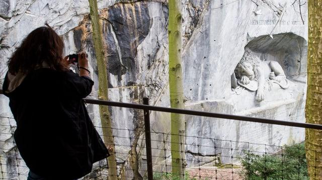Eine Touristin fotografiert das Löwendenkmal in Luzern.