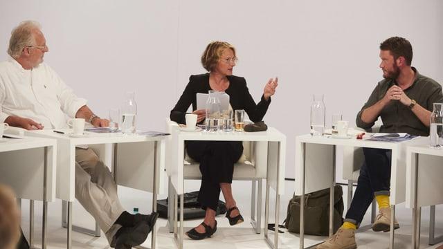 Drei Personen sitzen nebeneinander an Tischen und diskutieren.