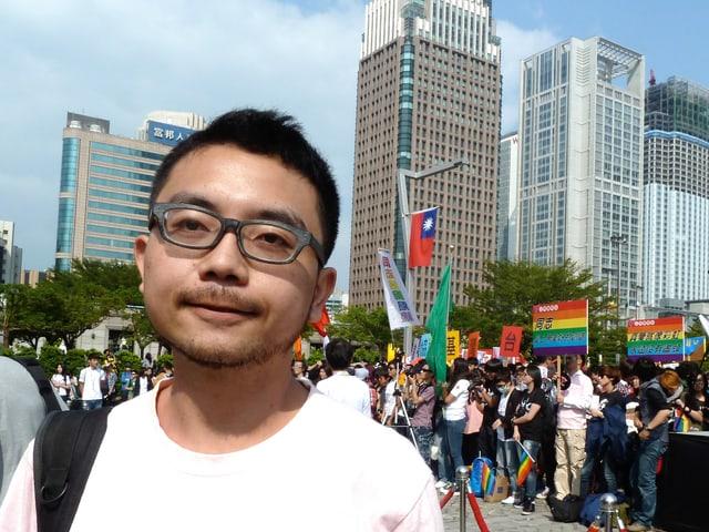 Ein junger Mann mit Brille steht vor einer Menschenansammlung, dahinter stehen moderne Hochhäuser.