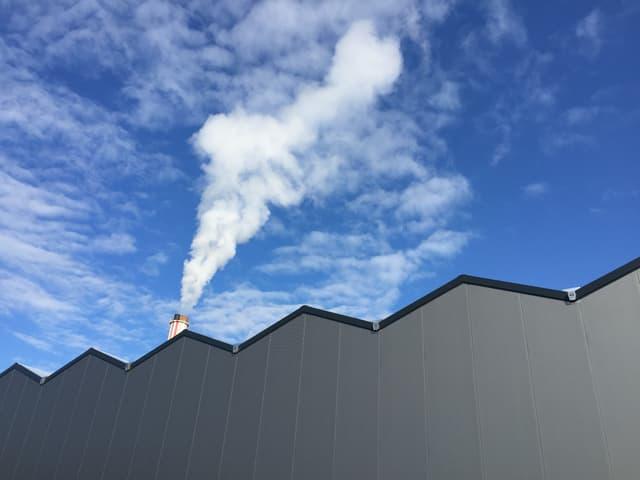 Blick an eine graue Wand einer grossen Lagerhalle mit einem rauchenden Kamin auf dem Dach.